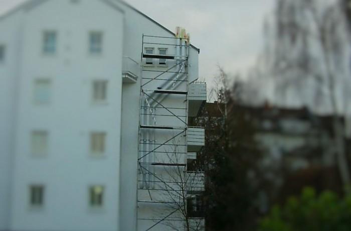 PVC Abluftleitung an Gebäudefassade, Abluftrohre in Fassadenfarbe lackiert
